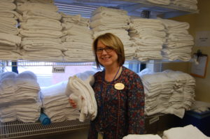 Family House volunteer prepares towels for guest rooms